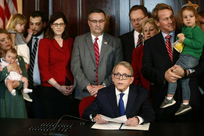 Gov. Mike DeWine speaks before signing a bill imposing one of the nation's toughest abortion restrictions, Thursday, April 11, 2019 in Columbus, Ohio. DeWine's signature makes Ohio the fifth state to ban abortions after the first detectable fetal heartbeat. That can come as early as five or six weeks into pregnancy, before many women know they're pregnant. (Fred Squillante/The Columbus Dispatch via AP)