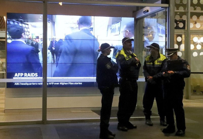 """In this Wednesday, June 5, 2019, photo, police officers stand in front of a television screen at the main entrance to the Australian Broadcasting Corp. building in Sydney. The head of Australia's public broadcaster said Friday, June 7, she has """"grave concern"""" about a recent police raid on the corporation's headquarters in connection with a 2017 story based on leaked documents that indicated the country's military forces were being investigated for possible war crimes in Afghanistan. (David Gray/AAP Image via AP)"""