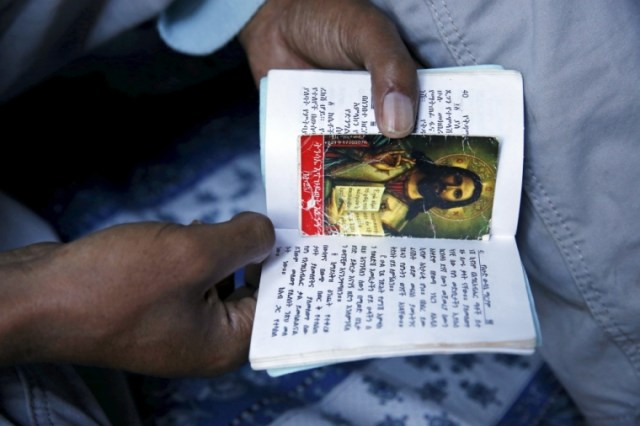 """Christian migrants from Eritrea and Ethiopia pray and read the bible before Sunday mass at the makeshift church in """"The New Jungle"""" near Calais, France, August 2, 2015. 