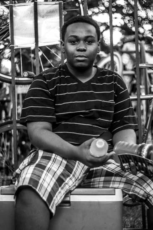 """""""Young Hawkers of Chicago"""" Another young boy hustling, however, alongside his older sister and siblings on the edge of the park. He was timid of conversation - and rightfully so. I realized after walking away that I, in fact, cut into his hustling time. The term """"everybody needs to eat"""" took on a new meaning after that moment."""