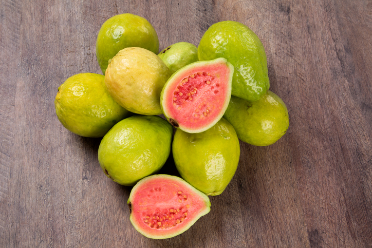 Some brazilian guavas over a wooden surface. Fresh fruits.