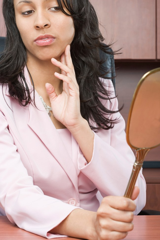 Businesswoman looking at a mirror