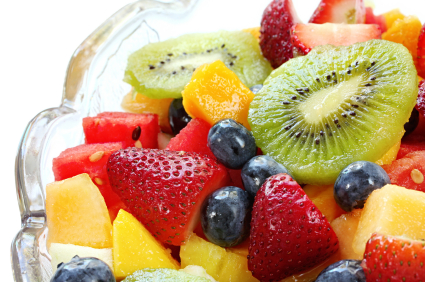A bowl of fruit salad with honey dressing
