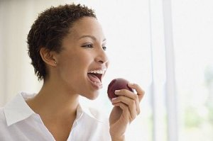 A woman eating a red apple