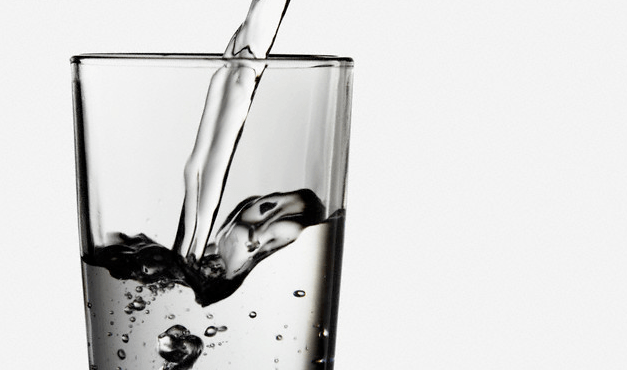 A glass of water pouring into a glass