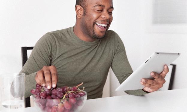 A man eating grapes and reading his iPad