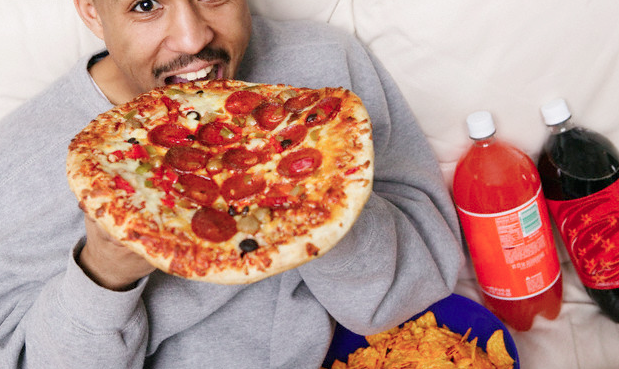 A man biting into a whole pizza while sitting on his sofa