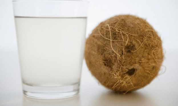 A glass of coconut water beside a whole coconut