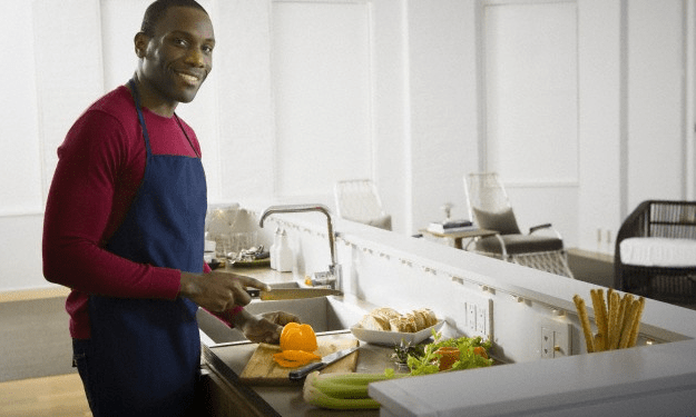 A man holding a yellow bell pepper in his kitchen