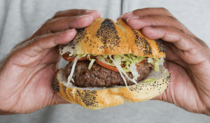 African American Black man's hands holding a burger