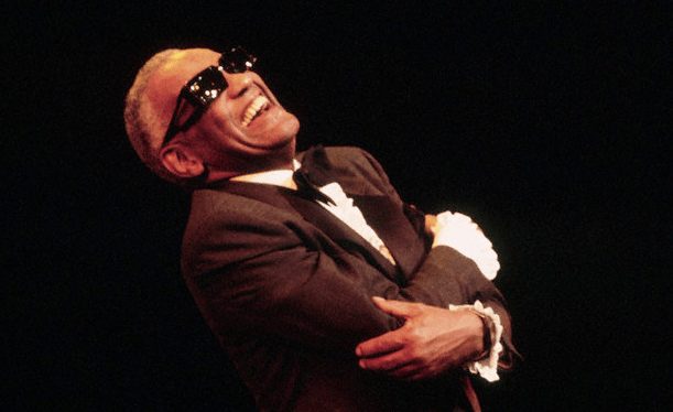 An image of Ray Charles, smiling, with his arms wrapped around himself