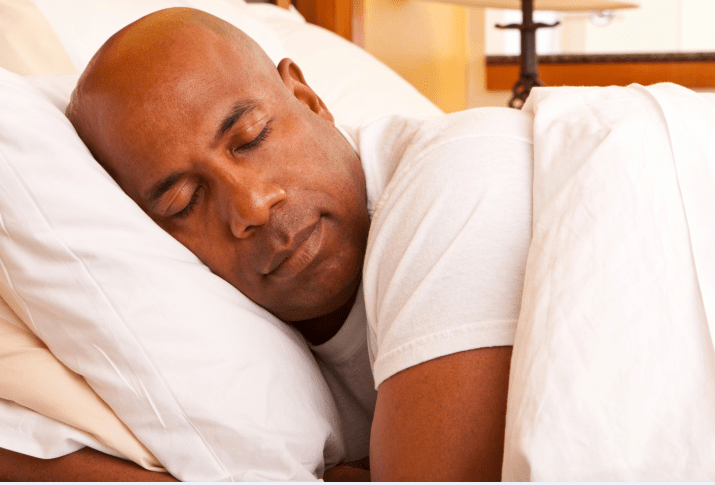 A man sleeping in his bed with his head on a pillow