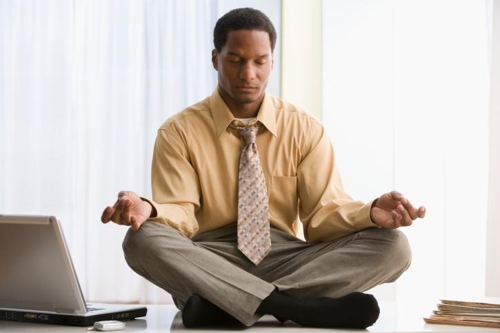 Black African American businessman meditating on desk