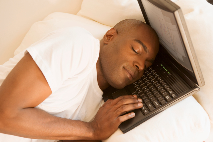 man sleeping on laptop