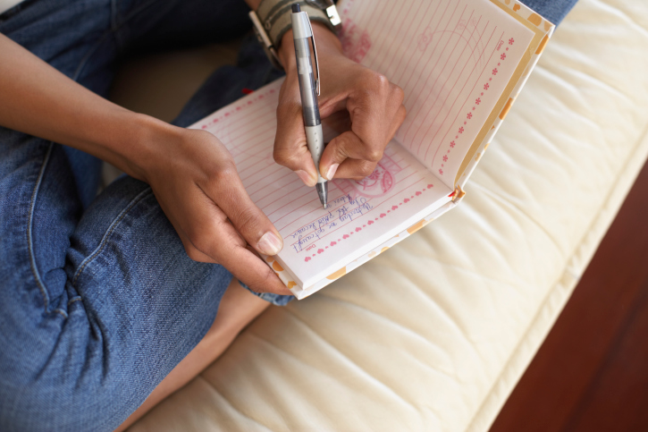 African American Black Woman's hands writing in journal