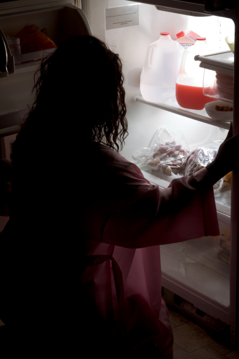woman kneeling in front of refridgerator at night