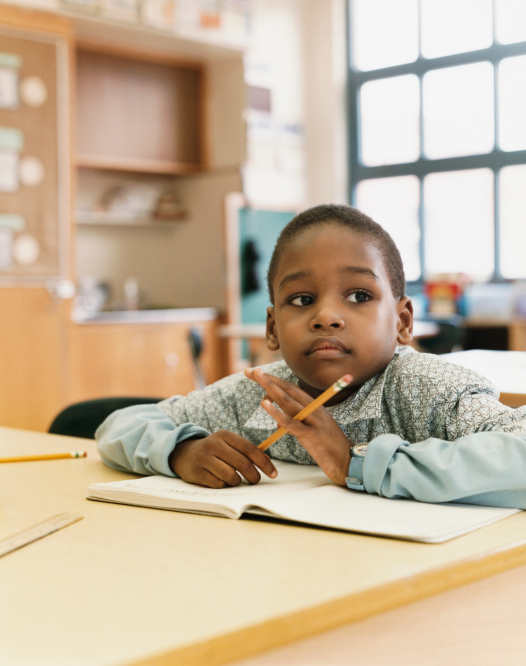 African American Black child sitting at classroom desk