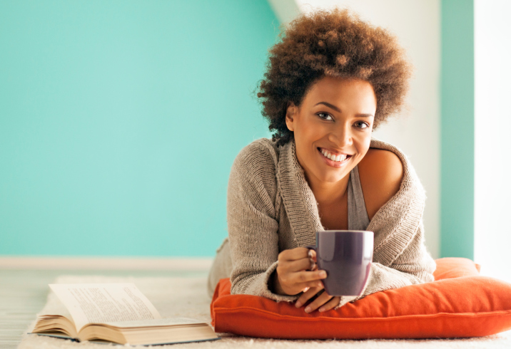 African American Black woman relaxing with cup of tea and book