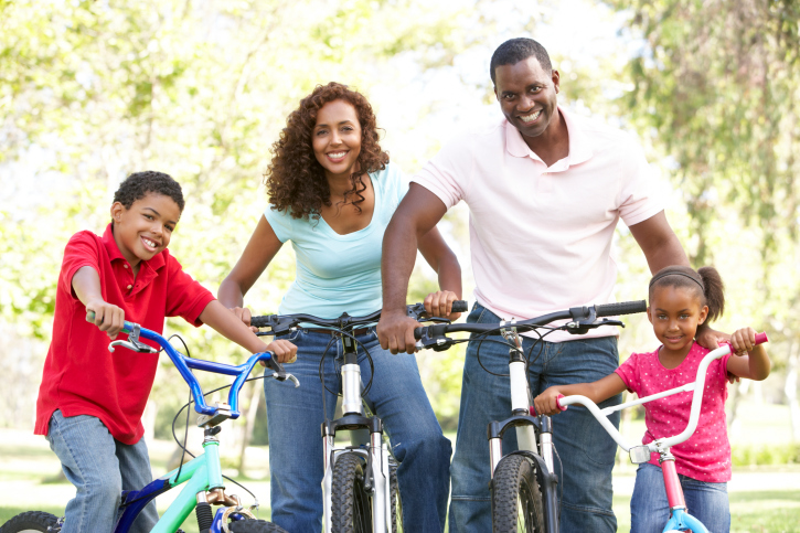 young family riding bikes in the park