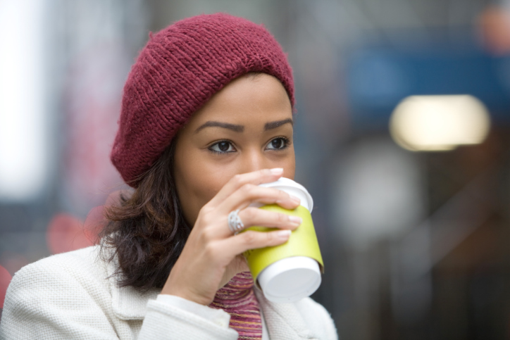 African American woman walking drinking coffee