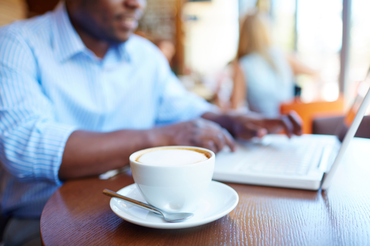 african american man sitting with a cup of coffee on the counter