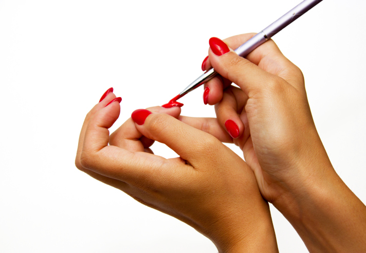 African American Black hands painting nails red