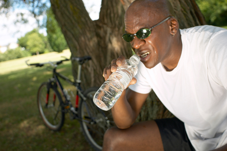 black man drinking water next to bike