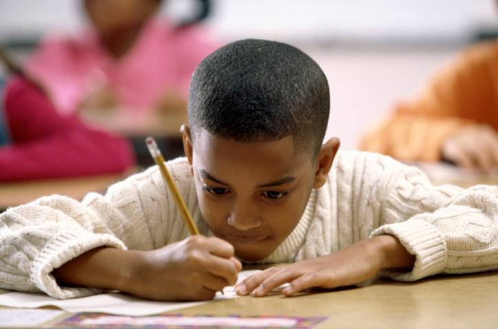 school boy writing at desk