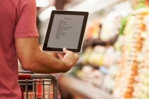 African American man grocery shopping with tablet