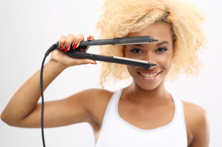 African American woman natural hair using flat iron