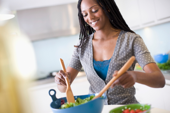 African American Black woman in kitchen mixing salad