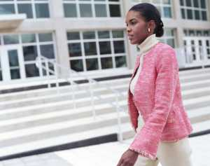 African American Black Businesswoman walking by office building, side view