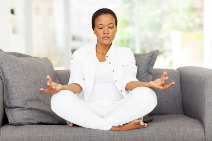 African American woman meditating on couch