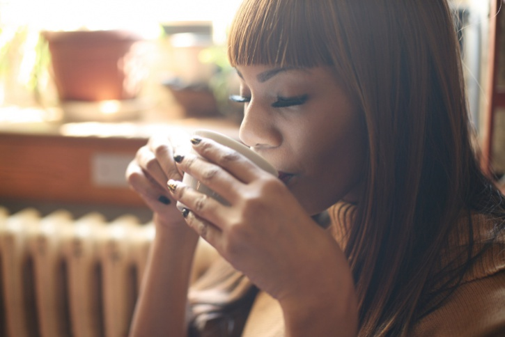 African American woman drinking from coffee tea cup