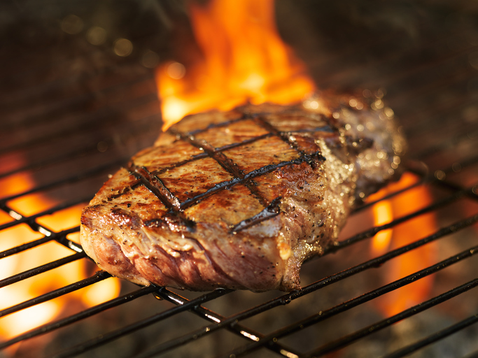 beef steak cooking over flaming grill