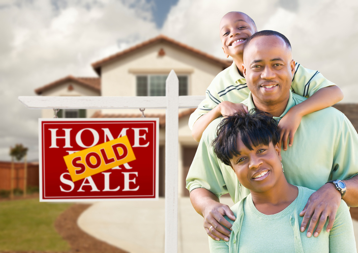 African American family in front of new house