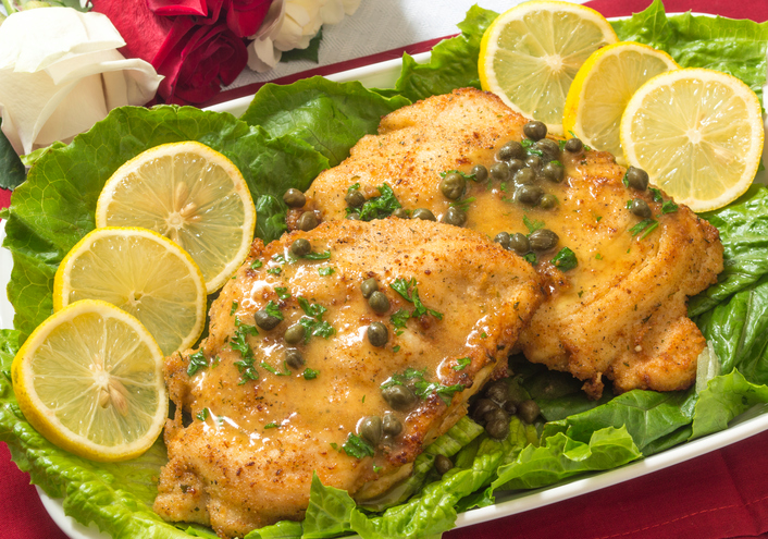 chicken piccata on a table with fresh roses