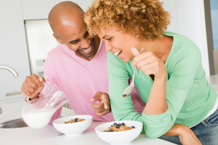 African American couple eating cereal breakfast
