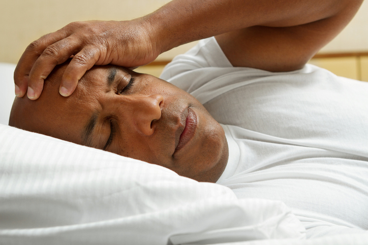 African American man in bed insomnia headache