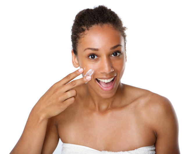 Close up portrait of a smiling african american woman applying lotion on skin