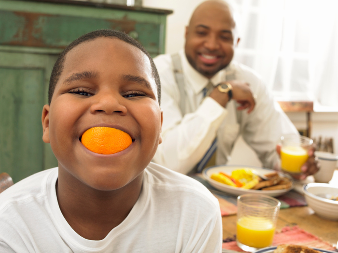 African American father and son eating breakfast