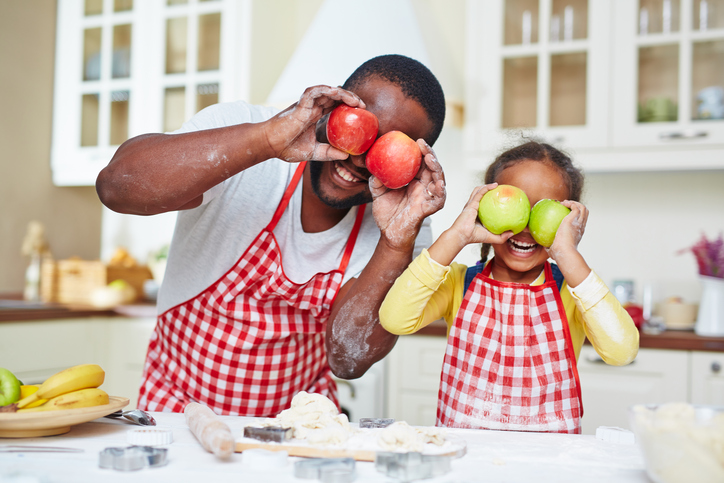 African American father and daughter cookingd