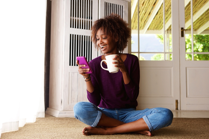 Portrait of a smiling young black woman sitting on floor at home with cell phone
