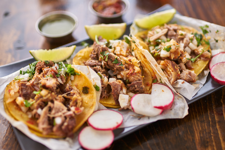 three street tacos in yellow corn tortilla with different meats, also has radishes