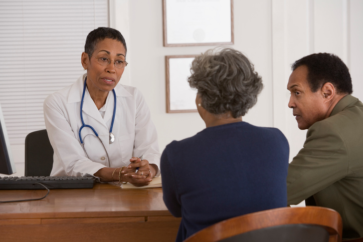 African American woman doctor speaking with couple