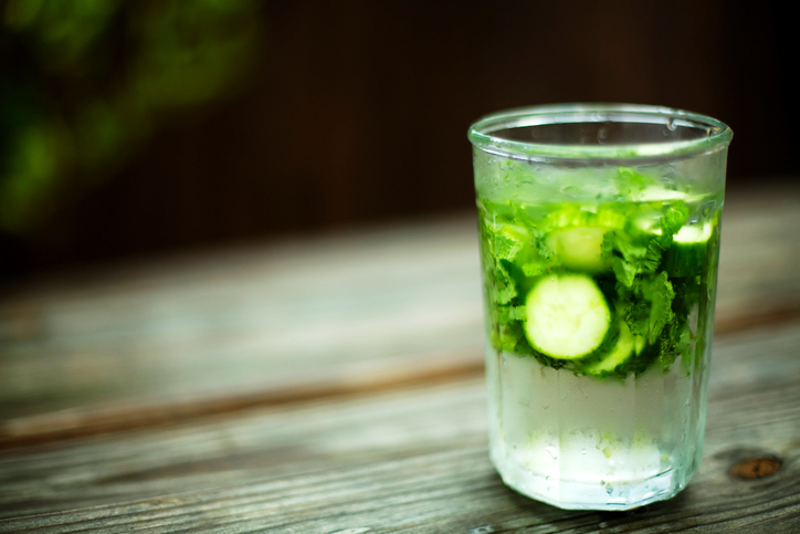 glass of iced water containing mint leaves and sliced cucumber placed on a rustic garden table