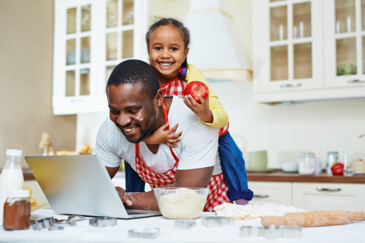 African American father and daughter cooking in kitchen