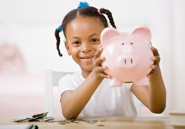African American girl puts money in piggy bank