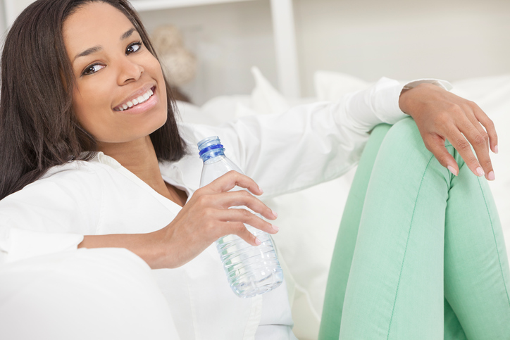 African American woman drinking bottled water