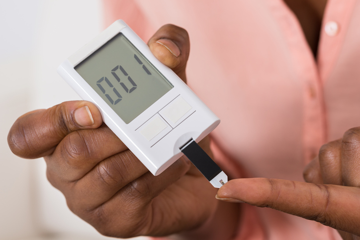 African American holding diabetes glucose meter with test strip
